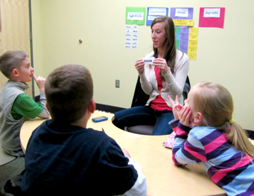 a teacher and students practicing reading concepts