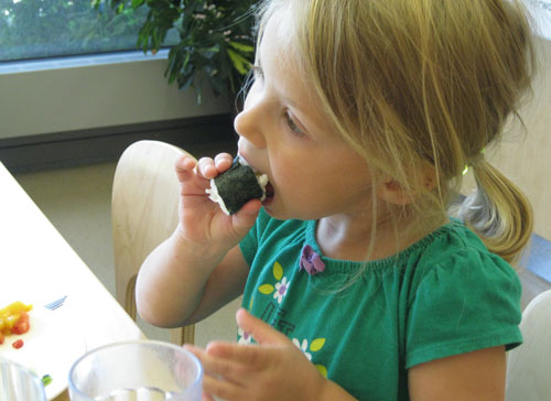 A young girl trying a piece of sushi