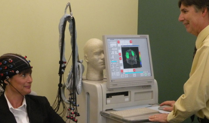 Near Infrared Spectroscopy Lab testing in progress: sensors on a researcher's head, another researcher at a computer with brain imagery on a computer screen
